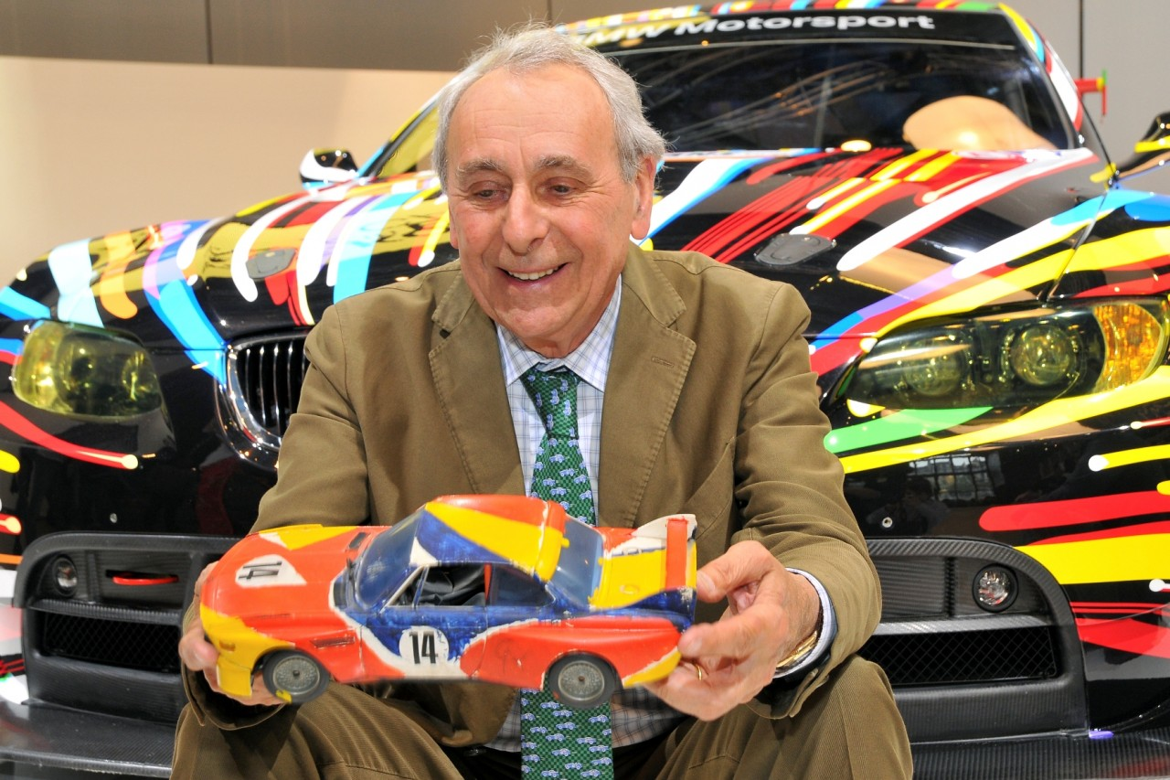 Hervé Poulain, Godfather of the Art Car Collection in front of the 17th BMW Art Car with a miniature of the first BMW Art Car by Alexander Calder in his hands (05/2010)